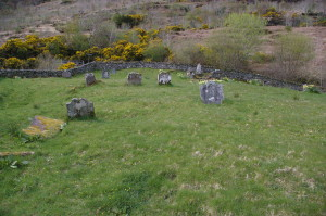 A handful of gravestones remain in the medieval churchyard of Kilmorich, surrounded by its enclosure wall.