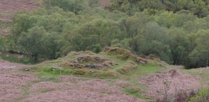 The remains of Fearnoch Chapel in its little enclosure, the land falling away into the woods below.