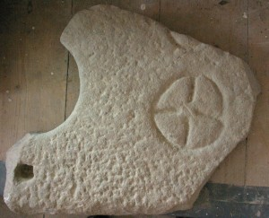 Part of a broken millstone, marked with a cross, may have served as a grave-marker at the early church of Lochgoilhead.