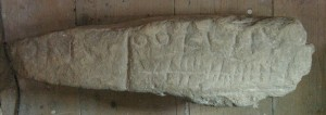 The other carved side of the stone bears an inscription, now illegible, in Roman letters and ogham.